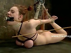 Redhead with big boobs hanged with hands above herself in filthy room used by man to fuck slaves